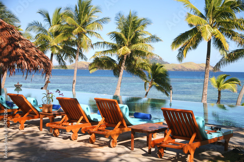 Fototapeta Stylish wicker furniture with blue cushions in an outdoor setting in a tropical location obraz