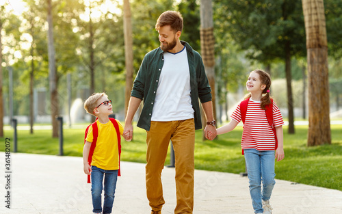 Children walking to school with father.