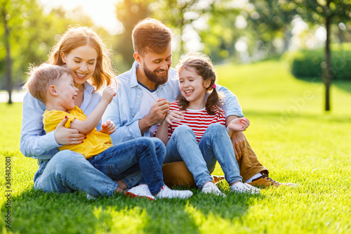 Happy family resting on lawn together.