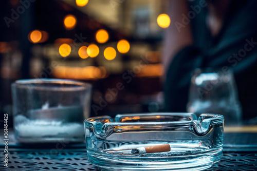 Photo Cigarette in a glass ashtray in a bar