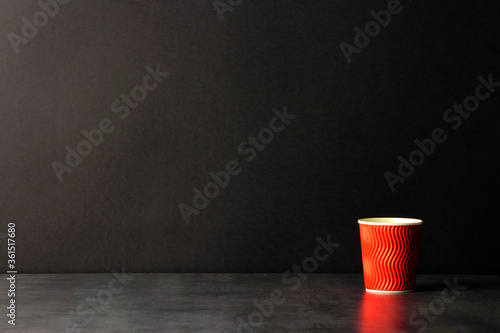 Foto red corrugated paper coffee cup on black background