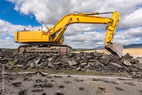 Fotomural Excavator repairing the asphalt of a road