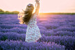 Happy woman dancing in a lavender field at sunset. Beautiful flowers meadow. Summer sunset colorful lighting