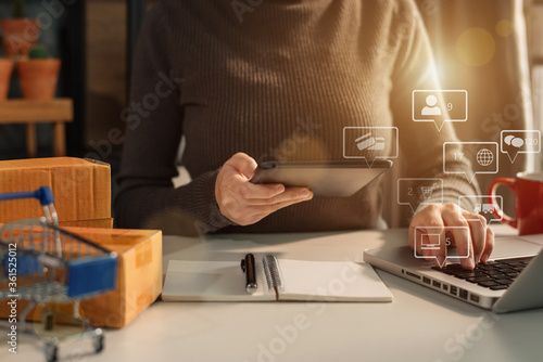 Photo Woman start up small business owner writing address on cardboard box at workplace