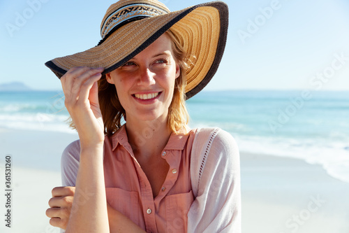Woman wearing hat smiling on the beach