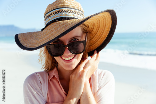 Portrait of woman wearing hat and sunglasses smiling