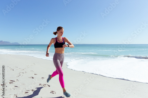 Woman checking time while running on the beach