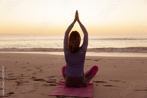 Rear view of woman performing yoga on the beach during sunset