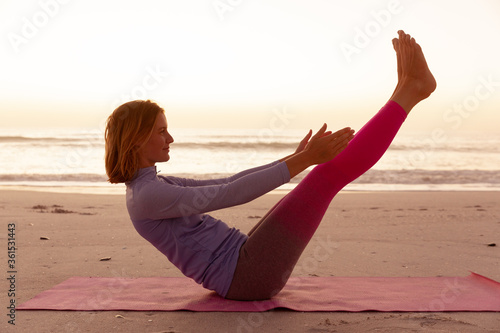 Woman performing yoga on the beach during sunset