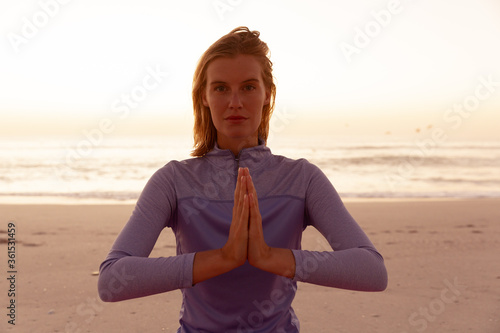 Portrait of woman performing yoga on the beach during sunset