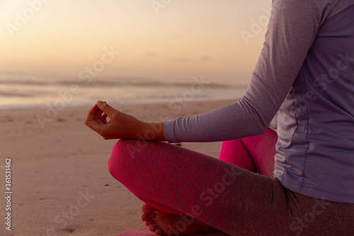 Mid section of woman performing yoga on the beach during sunset