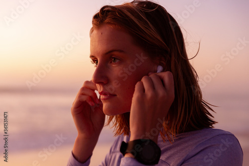 Beautiful woman wearing earphones on the beach