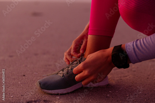 Low section of woman tying her shoelaces on the beach