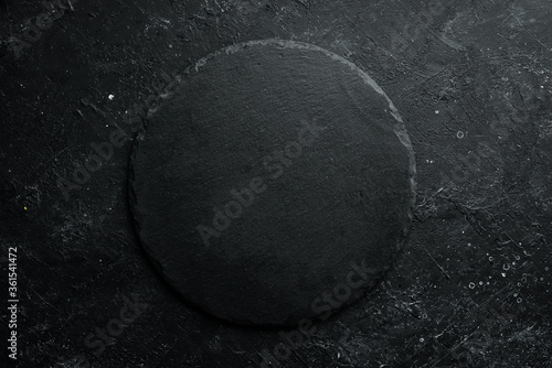Black stone round slate plate on a black stone background Canvas Print
