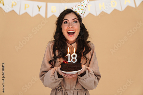 Papel de parede Image of excited young woman smiling while posing with birthday cake
