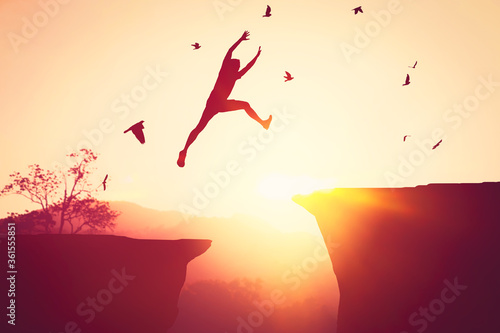 Photo Silhouette man jumping between cliff at top of mountain background with birds flying