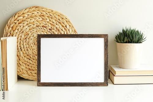 Obraz Boho style empty photo frame, dark wood frame mockup, horizontal wooden sign mock-up for artwork, bohemian interior, books, plant on white shelf. - fototapety do salonu