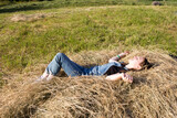 A young woman or teenage girl is lying on the hay, dreaming, resting. Holidays, summer mood, Sunny summer day.