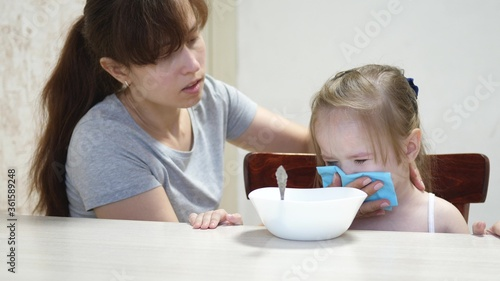 Mom calms a capricious child sitting at the table Tablou Canvas