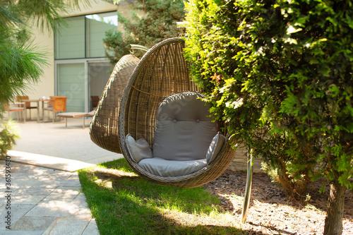 Fototapeta Well-kept green garden. Great cozy place to stay. Wicker Chair Nest obraz