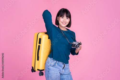 Fototapeta Traveling and tourism, Asian cute girl holding backpack suitcase and camera, on journey travel exploration adventure visit holiday vacation packing luggage on pink isolated background copy space obraz