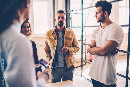 Skilled male leader of working team having informal meeting with employees check Fototapet