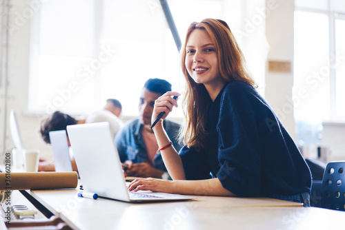 Fotografia Portrait of charming young female software developer working in modern office wi