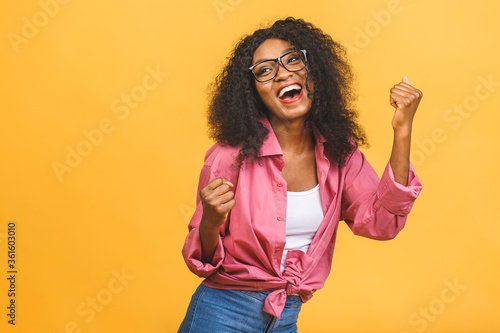 Fotografie, Tablou Happy winner! Young African American black woman isolated on yellow background giving a thumbs up gesture