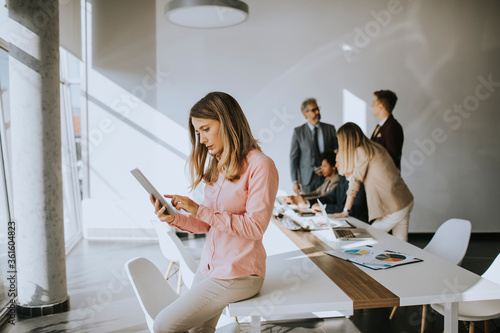Fototapeta Young business woman using digital tablet in the office obraz