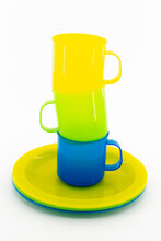 Three Colored Mugs And Three Colored Saucers On A White Background