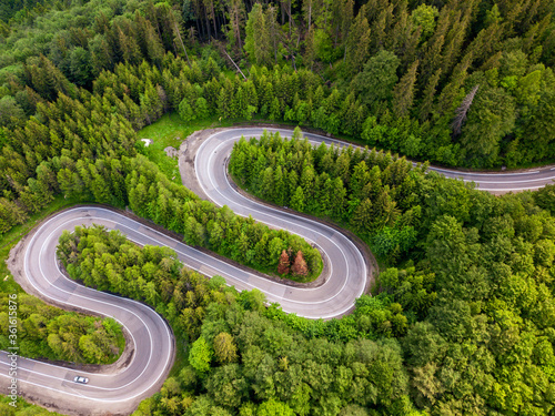 Obraz na plátně Aerial view of a green forest and an empty road traffic