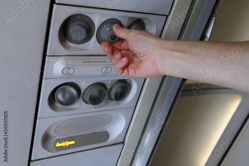 Photo mano regulando el aire acondicionado en un avión