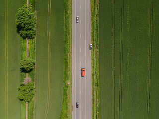 Aerial view of a red car driving on rural country road