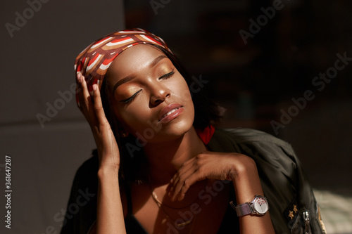 Obraz Lifestyle outdoor portrait of beautiful pretty stylish sensual african woman wearing jeans and shirt sitting and relaxing. - fototapety do salonu