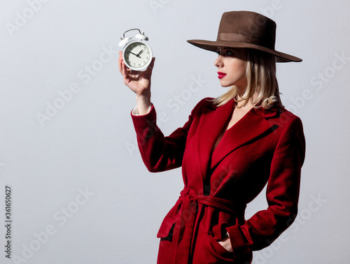 Blonde girl in red coat and vintage hat with alarm clock