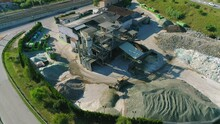 Top View Drone Shot Over The Glass Recycling Plant. The Wheel Loader Drops The Grained Glass In Slow Motion. 4K Footage.