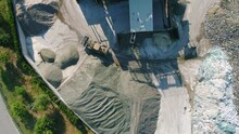 Drone Footage Over The Glass Recycling Plant. The Wheel Loader Transports Piles Of Broken Glass.