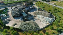 Drone Footage Of The Glass Recycling Factory. The Yellow Wheel Loader Forms The Pile Of Grain Glass.