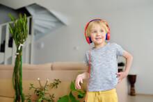 Preschooler Child Enjoy Listen Music Or Audiobook Using His Headphones At Home.