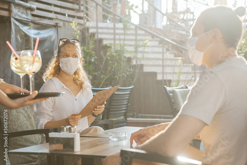 Couple with medical facemask are keeping social distance in restaurant Wallpaper Mural