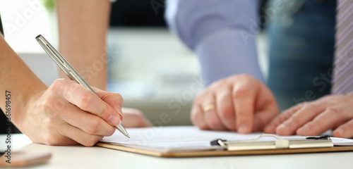 Female arm offer contract form on clipboard pad and silver pen to sign closeup Wallpaper Mural