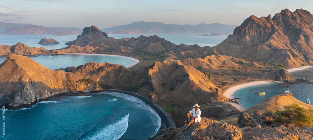 Fototapeta Young Asian man traveller standing on top view of Padar island in a morning sunrise in summer season, Komodo national park in Flores island, Indonesia. panoramic banner portion