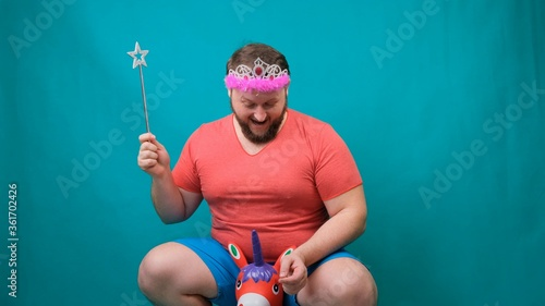Photo handsome bearded freaky man in a pink T-shirt with a diadem on his head is riding astride a unicorn with a magic wand in his hand