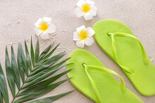 Stylish Flip-flops, Flowers And Tropical Leaf On Sand