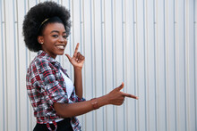 Promotion Concept. Cheerful African American Girl Pointing Aside On Free Space, Recommending Something. Grey Background..