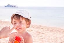 Hand Of Caucasian Mother Applying Suncream  To Her Son On Beach.