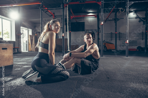 Fototapeta Beautiful young sporty couple workout in gym together. Caucasian man training with female trainer. Concept of sport, activity, healthy lifestyle, strength and power. Working out ABS. Inclusion. obraz