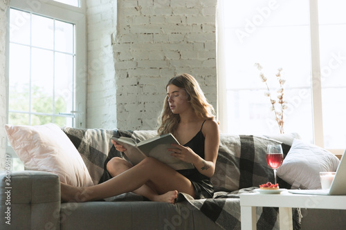 Reading magazine. Portrait of pretty young girl in modern apartment in the morning. Resting, calm, salisfied. Youth and wellness concept. Elegance woman in silk dress spending time comfortable.