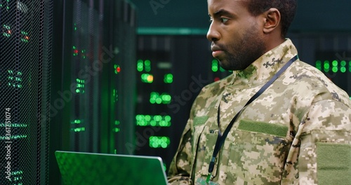 Canvastavla Close up of African American male army technician in camouglage costume and hat typing on keyboard of laptop computer while working with secret data at server room
