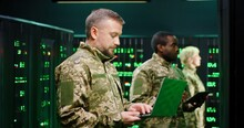 Caucasian Military Male Officer In Camouflage Standing In Server Room With Laptop Computer And Checking Data On Monitors. Work With Secret Info In Army. Digital Concept. African American Man Behind.